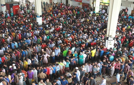 People stand in long queues at counters of Kamalapur Railway Station..